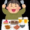 カロリーの高そうな食べ物の前でナイフとフォークを振り上げている男性の絵