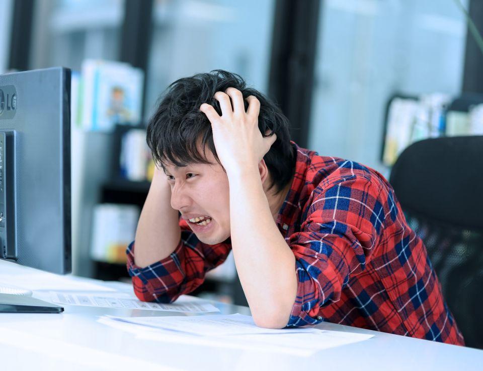 パソコンの画面の前で頭を抱えてる人
