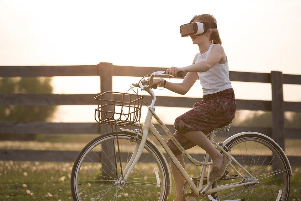 VRヘッドギアを付けて自転車に乗る女性